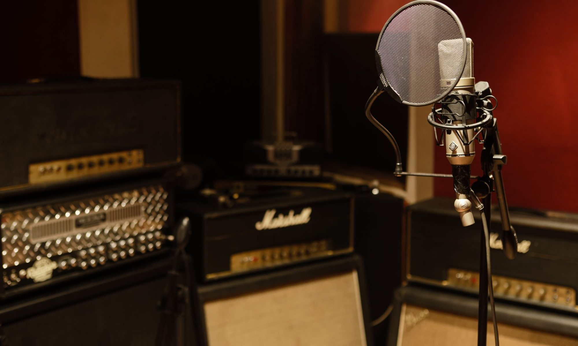 Photo taken by Andy Lund of Neumann U87 microphone with guitar amplifiers in background